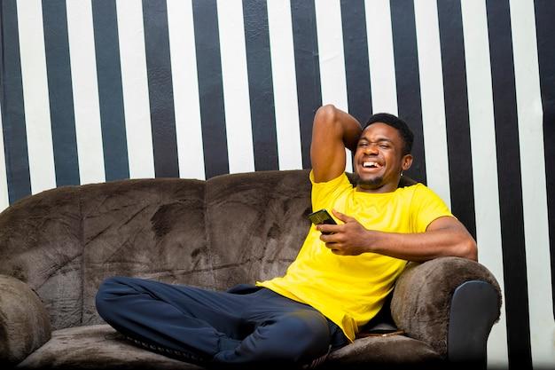 집에 앉아 있는 동안 모바일 장치를 사용하여 소셜 네트워크에서 친구와 채팅하는 젊은 흑인 남성 힙스터