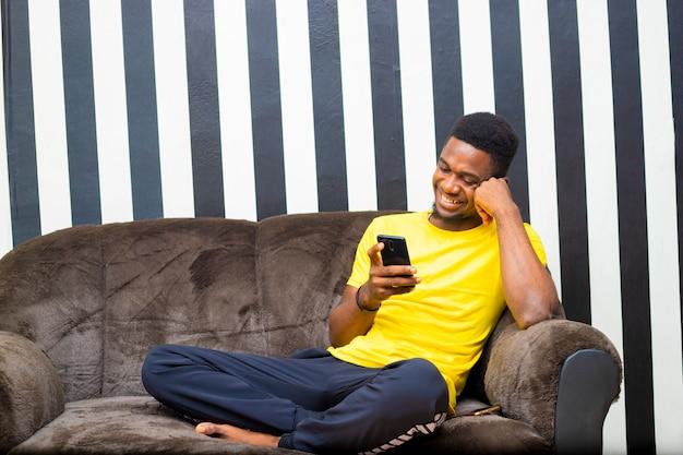모바일 장치를 사용하여 집에서 쇼핑하는 젊은 흑인 아프리카 남성