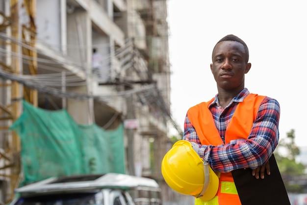 Молодой темнокожий африканец на стройке с буфером обмена в шлеме