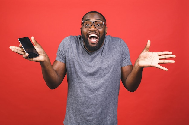 Young black african man, holding blank smartphone, showing screen, feeling happy and surprised