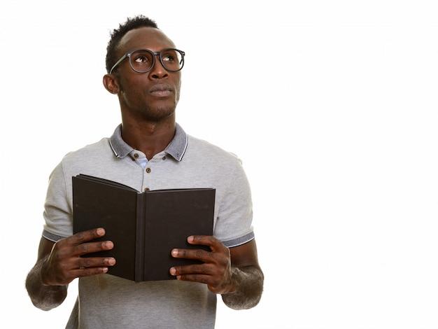 考えながら本を持っている若いアフリカ黒人男性
