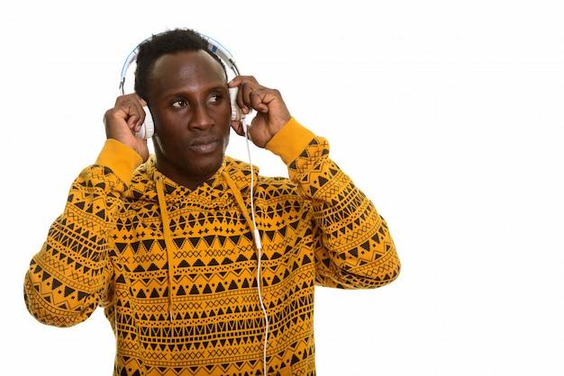 ヘッドフォンを押しながら音楽を聴く若いアフリカ黒人男性
