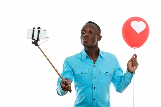 Молодой темнокожий африканец держит красный воздушный шар с сердечным баллоном