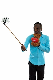 Young black african man holding teddy bear with heart and love heart