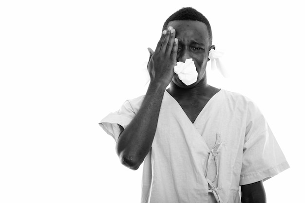 Young black african man patient having headache and looking sick with tissues in his ears and nose