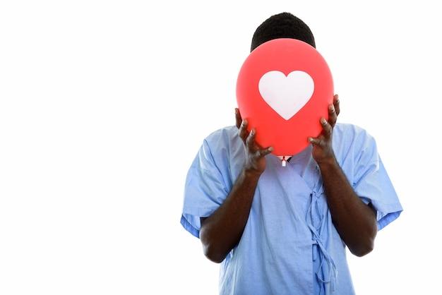 Молодой темнокожий африканец, пациент, пряча лицо за воздушным шаром в форме сердца