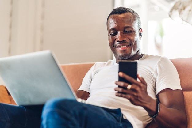 Молодой темнокожий африканец, расслабляющий, используя портативный компьютер, работая и встречу по видеоконференции дома. молодой творческий африканский человек разговаривает с гарнитурой. работа из дома концепции