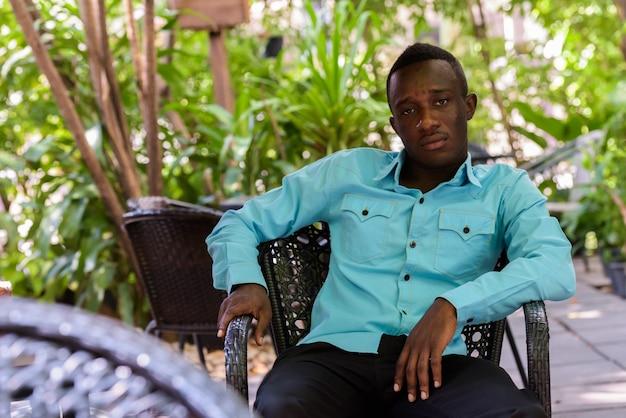 Молодой темнокожий африканец, сидя в кафе на открытом воздухе surrounde