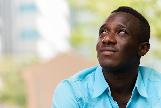 Молодой черный африканец сидит, думая и глядя на улицу