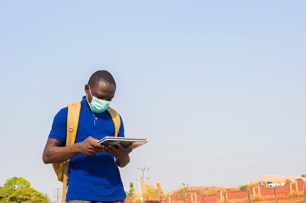 Young black african man student carrying schoolbag wearing face mask checking internet using tablet