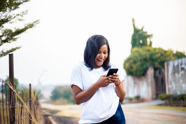Young black african millennial women using smart phone chatting online with friends on social media