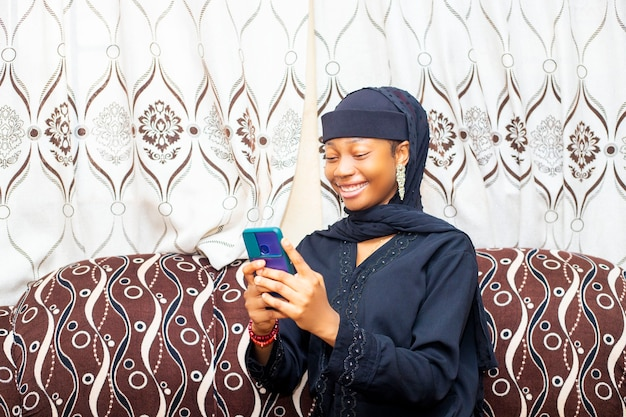 휴대 전화를 사용하여 친구와 온라인 채팅을 하는 젊은 흑인 아프리카 이슬람 여성