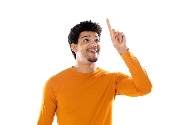 笑って、白い背景で隔離の彼の指で何かを指している若い黒人のアフロ男