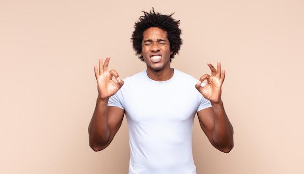 젊은 흑인 아프리카 남자가 한 손으로 무서워하거나 불안해하고 궁금해하거나 맹목적으로 놀람을 기다리고있는 눈을 가리고 있습니다.