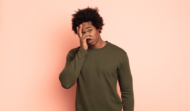 Молодой черный афро-мужчина чувствует скуку, разочарование и сонливость после утомительной, скучной и утомительной работы, держа лицо рукой