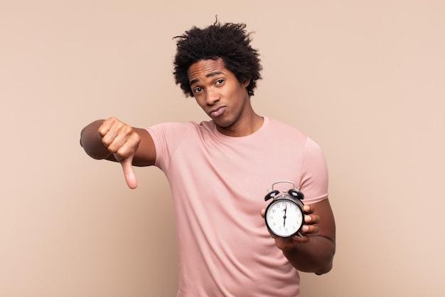 Молодой черный афро-мужчина чувствует раздражение, злость, раздражение, разочарование или недовольство, показывая большой палец вниз серьезным взглядом