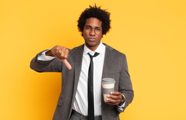 十字架、怒り、イライラ、失望、または不満を感じ、真剣な表情で親指を下に見せている若い黒人のアフロ男