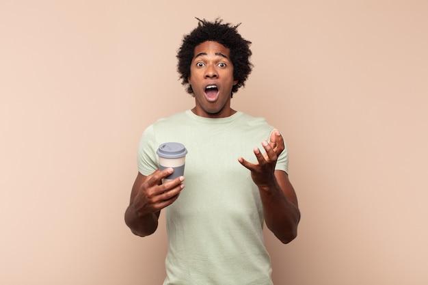 若い黒人のアフロ男は、ストレスと恐怖の表情で、非常にショックを受け、驚き、不安とパニックを感じています
