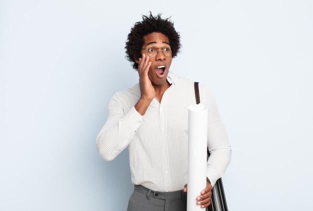 행복하고, 흥분하고, 놀란 느낌, 얼굴에 양손으로 측면을 찾고 젊은 흑인 아프리카 남자