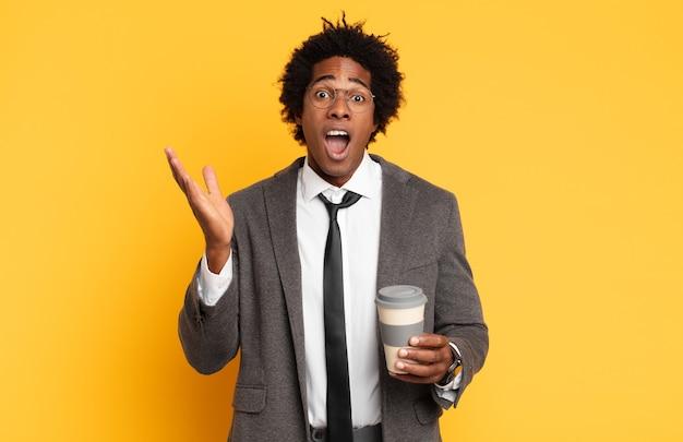 信じられないほどの何かに幸せ、興奮、驚き、またはショックを受け、笑顔で驚いた若い黒人のアフロ男