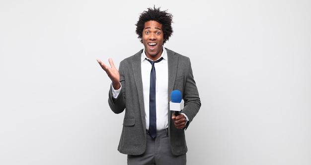 Молодой черный афро-мужчина чувствует себя счастливым, взволнованным, удивленным или шокированным, улыбается и удивляется чему-то невероятному