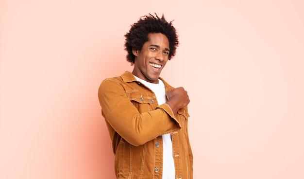 Молодой черный афро-мужчина чувствует себя счастливым, позитивным и успешным, мотивированным, когда сталкивается с проблемой или празднует хорошие результаты