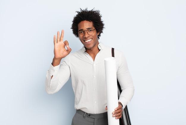 젊은 흑인 아프리카 남자가 행복하고 편안하고 만족스럽고 괜찮은 제스처로 승인을 보여주는 미소