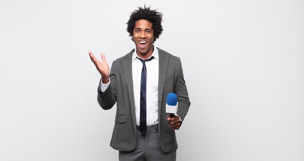 幸せ、驚き、陽気を感じ、前向きな姿勢で笑って、解決策やアイデアを実現する若い黒人アフロ男