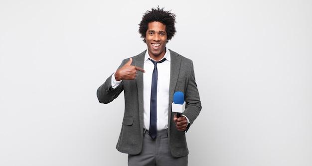 Молодой черный афро-мужчина чувствует себя счастливым, удивленным и гордым, указывая на себя взволнованным, изумленным взглядом