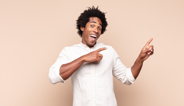 Young black afro man feeling joyful and surprised, smiling with a shocked expression and pointing to the side