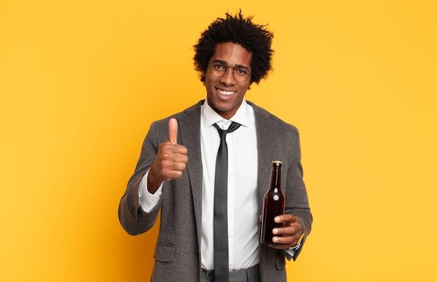 자랑스럽고, 평온하고, 자신감 있고, 행복하고, 엄지 손가락으로 긍정적으로 웃고있는 젊은 흑인 아프리카 남자