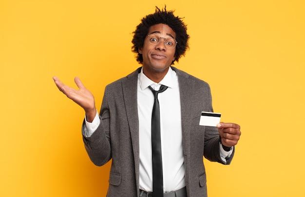 젊은 흑인 아프리카 남자가 의아해하고 혼란스럽고 의심스럽고 가중하거나 재미있는 표현으로 다른 옵션을 선택하는 느낌
