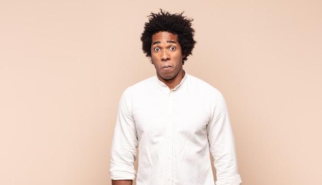 悲しくてストレスを感じている若い黒人のアフロ男、悪い驚きのために動揺し、否定的で不安な表情で