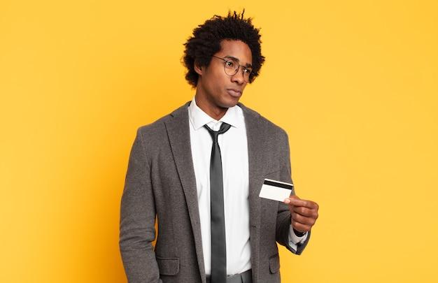 젊은 흑인 아프리카 남자가 슬프고 화 나거나 화가 나고 부정적인 태도로 측면을 바라보고 의견이 일치하지 않습니다.