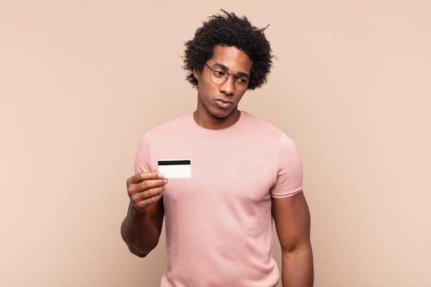 젊은 흑인 아프리카 남자는 슬프고, 화가 나거나, 화가 나고, 부정적인 태도로 측면을 바라보고, 불일치에 찌푸리고