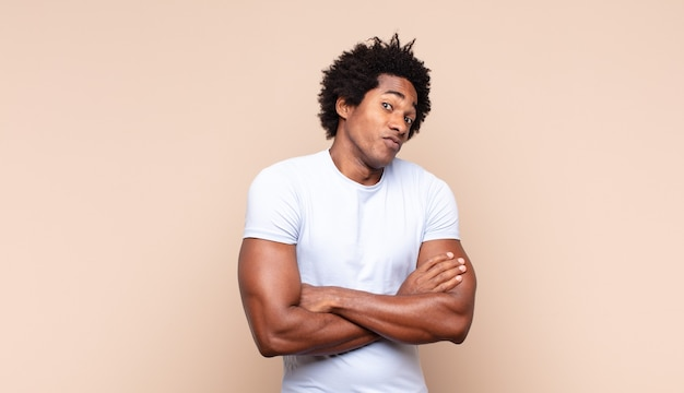 Young black afro man feeling serious, thoughtful and concerned, staring sideways with hand pressed against chin