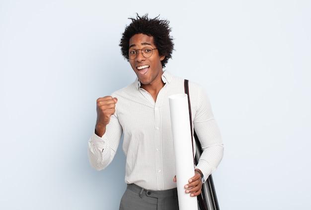 젊은 흑인 아프리카 남자는 충격을 받고 흥분하고 행복하며 웃고 성공을 축하하며 와우라고 말합니다!
