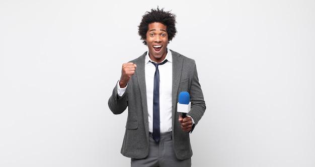Молодой темнокожий афро-мужчина потрясен, взволнован и счастлив, смеется и празднует успех, говоря: