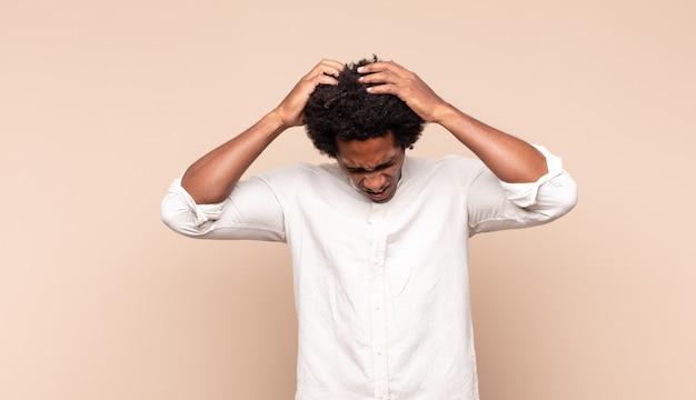 Молодой черный афро-мужчина чувствует стресс и разочарование, поднимает руки к голове, чувствует себя усталым, несчастным и страдает мигренью