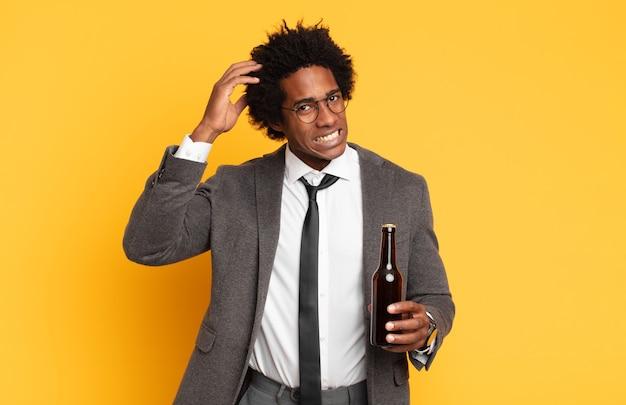 Молодой черный афро-мужчина чувствует стресс, беспокойство, беспокойство или испуг, с руками за голову, паникует из-за ошибки