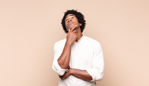 思慮深く、疑問に思ったり想像したり、空想にふけったり、コピースペースを見上げたりする若い黒人のアフロ男