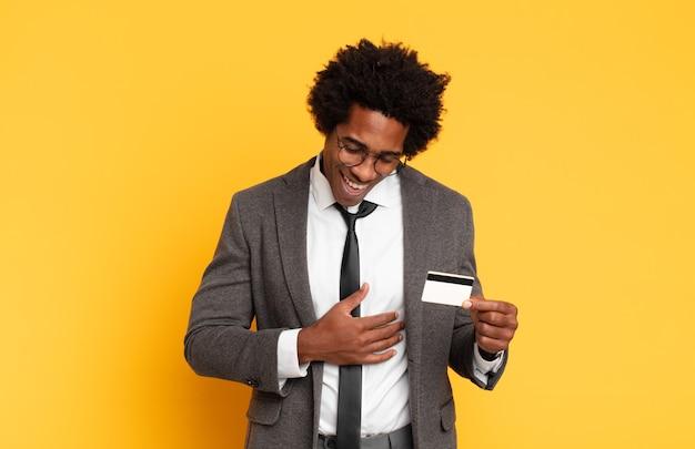젊은 흑인 아프리카 남자가 재미있는 농담에 크게 웃고, 행복하고 쾌활한 느낌, 재미