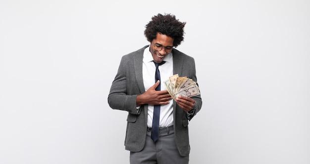젊은 흑인 아프리카 남자는 재미있는 농담, 행복하고 쾌활한 느낌, 재미를 느끼며 큰 소리로 웃고 있습니다.