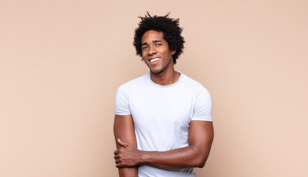 恥ずかしがり屋で元気に笑う若い黒人のアフロ男、友好的で前向きだが不安な態度
