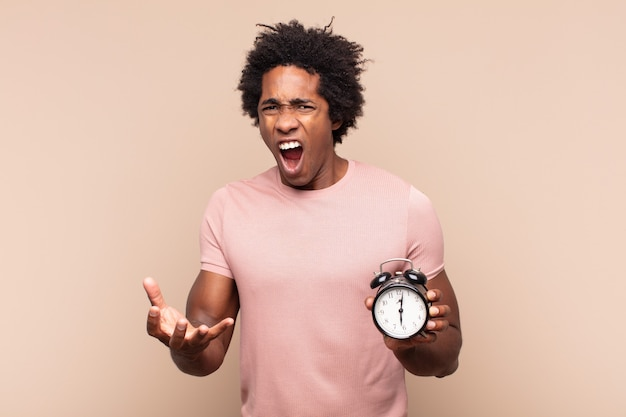 Young black afro man looking angry, annoyed and frustrated screaming wtf or what's wrong with you