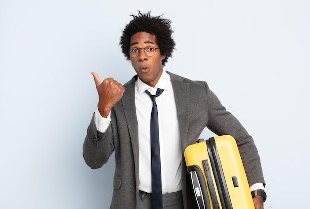 불신에 놀란 젊은 흑인 아프리카 남자, 옆에있는 물건을 가리키고 와우, 믿을 수 없다고 말하는