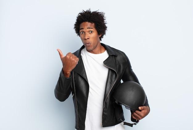 信じられないことに驚いた若い黒人のアフロ男が、横の物体を指差して、すごい、信じられない、と言った