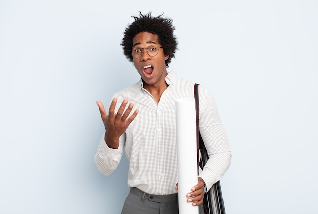 젊은 흑인 아프리카 남자가 절망적이고 좌절감을 느끼고 스트레스를 받고 불행하고 짜증이 나서 소리 지르고 비명을 지르고 있습니다.