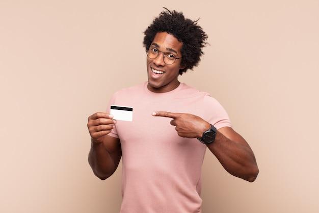 젊은 흑인 아프리카 남자는 공간을 복사하기 위해 옆과 위쪽을 가리키며 흥분하고 놀란 것처럼 보입니다. 프리미엄 사진