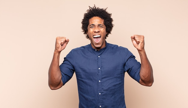 幸せでフレンドリーに見え、笑顔で前向きな姿勢であなたに目をまばたきしている若い黒人のアフロ男